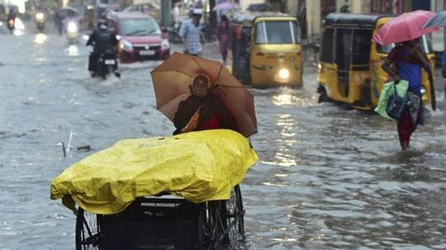 An elderly woman pushes her cart on a waterlogged road during heavy rains triggered by Cyclone Nivar in Chennai on Tuesday.(PTI Photo)