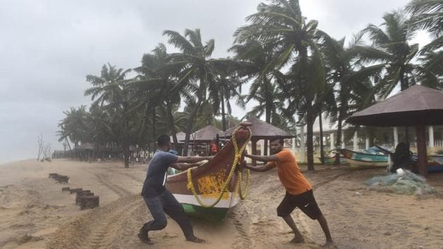 Fishermen move their boats to a safer place near Mamallapuram before Cyclone Nivar makes landfall at about midnight.(PTI PHOTO.)