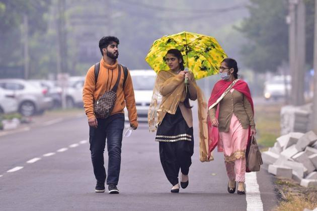 Commuters walk in drizzle in Ludhiana on Wednesday.(Gurpreet SIngh/HT)