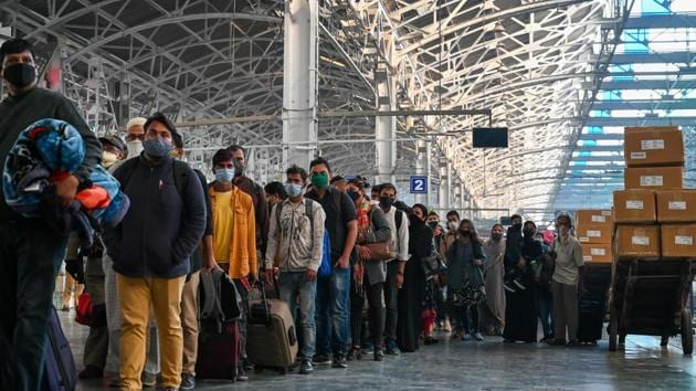 Passengers queue at a platform for Covid-19 screening after arriving from New Delhi at the railway station in Mumbai on November 25. As part of renewed stringency, some states have enforced mandatory tests on inter-state commuters from Delhi which is currently in going through its third wave of infections. Uttarakhand joined states like Maharashtra and Uttar Pradesh in mandating this measure on November 25. (Punit Paranjpe / AFP)