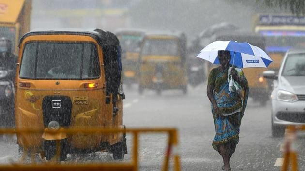 """A woman walks under an umbrella during heavy rains in Chennai on Tuesday as Cyclone Nivar approaches the southeastern coast. The Indian Meteorological Department has said Cyclone Nivar is set to cross the coasts of Tamil Nadu and Puducherry as a """"very severe cyclonic storm"""" late on Wednesday.(AFP Photo)"""
