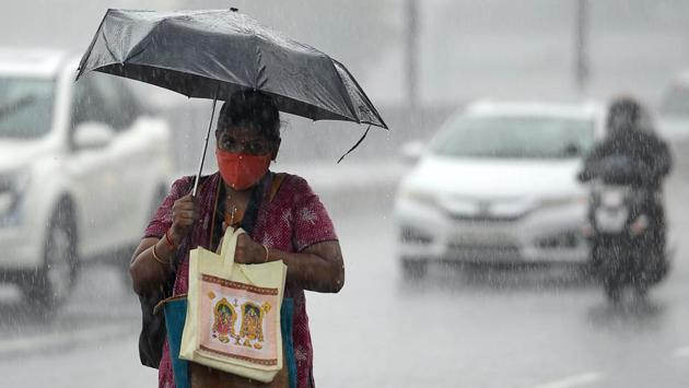 A woman walks under an umbrella during heavy rains as cyclone Nivar approaches the eastern Indian coast, in Chennai on November 24. After remaining below 39,000 for three days last week, daily COvid-19 cases again soared past 40,000 daily and have been on the rise since, HT reported. (Arun Sankar / AFP)