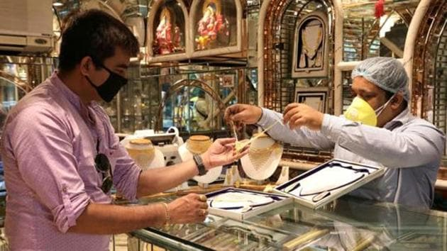 A salesman shows gold necklaces to a customer at a jewellery showroom in Kolkata in this file photo.(Reuters Photo)