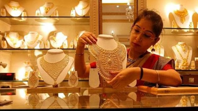 A saleswoman displays a gold necklace inside a jewellery showroom in Kolkata.(Reuters File Photo)