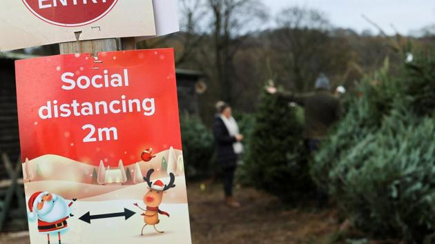 A social distancing sign is pictured as people visit a Christmas Tree Farm.(Reuters)