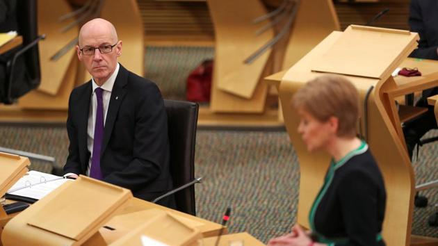 Scottish Deputy First Minister and Cabinet Secretary for Education John Swinney looks at First Minister Nicola Sturgeon as she makes a statement to the Scottish Parliament.(Reuters)