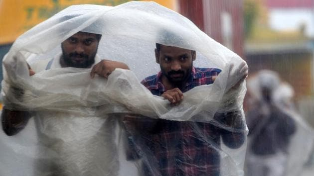 People use plastic sheets to cover from heavy rains in Chennai as cyclone Nivar approaches the southeastern coast of the country on November 25, 2020.(AFP)