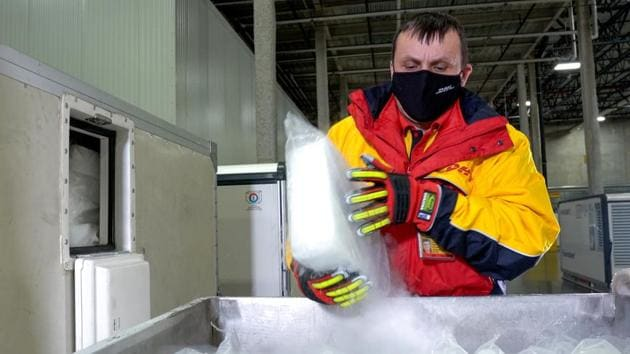 "A DHL worker loads dry ice into ""Envirotainers"" inside an ultra-cold facility that is used for the shipment of vaccines, medical supplies and pharmaceuticals in Chicago, Illinois.(VIA REUTERS)"