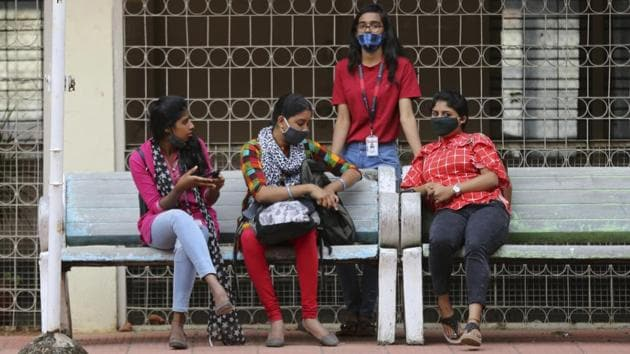 Students wearing face masks as a precaution against the coronavirus spend time between their classes.(AP file photo)
