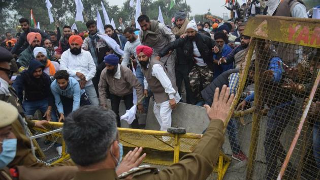Farmers break past police barricades while marching towards Delhi, at Ambala on November 25. The march picked up steam on November 25, when multi-layer barricades on Punjab's borders with Haryana were demolished by farmers using tractors as they continued their march towards the capital. (HT Photo)
