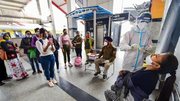 A health worker, wearing protective gear, collects swab sample of a passenger at Nizamuddin Railway Station in New Delhi.(PTI)