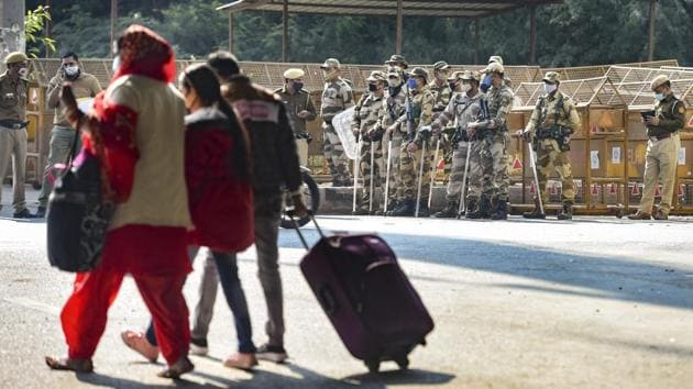 People walk past police personnel at Delhi-Ghaziabad border in Ghazipur, New Delhi on November 26. The farmers are scheduled to reach Delhi through five highways connecting the city. Deputy commissioner of police and Delhi Police spokesperson Eish Singhal has said that so far the situation is normal and police forces along with anti-riot force and paramilitary personnel are deployed adequately at all border areas, HT reported. (Vijay Verma / PTI)