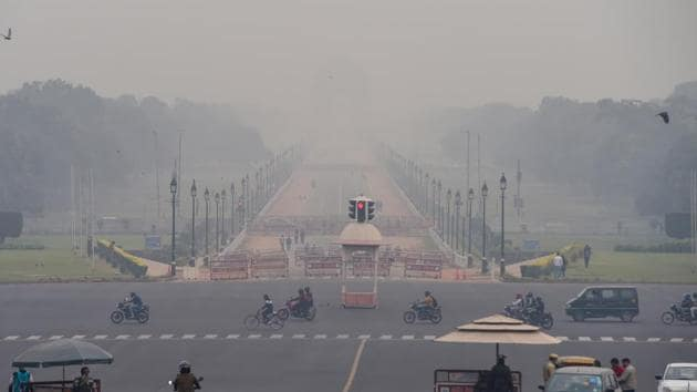 Vehicles ply at Vijay Chowk amid low visibility due to smog, in New Delhi.(PTI)