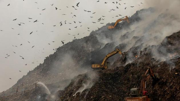 Firefighters and excavators try to douse fire as smoke billows from burning garbage at the Ghazipur landfill site in New Delhi.(REUTERS)