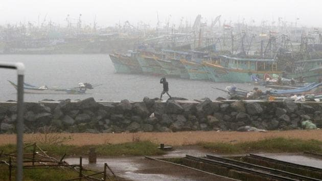 A man walks amid rain at the Kasimedu Harbor on the Bay of Bengal coast in Chennai on November 25. Tamil Nadu state authorities issued an alert and asked people living in low-lying and flood-prone areas to move to safer places. (R Parthiban / AP)