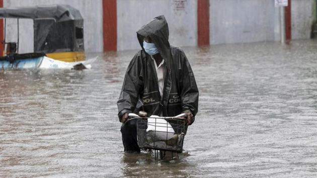 A man wearing a mask as a precaution against the coronavirus pedals his cycle through a flooded street in Chennai on November 25. Cyclonic winds brought nearly 237 mm of rainfall to Puducherry until 2.30am on November 25. Cuddalore recorded 246 mm rainfall, while Chennai and Karaikal received 89 mm rainfall due to the storm. (R. Parthibhan / AP)