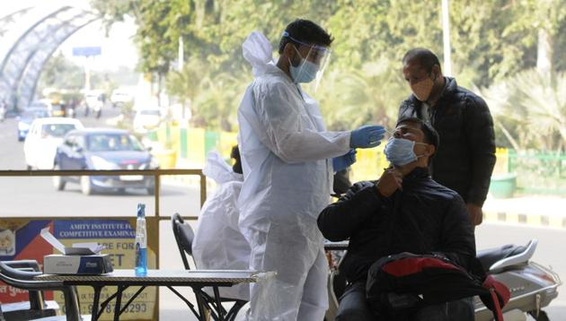 A medical worker collects a sample from a commuter arriving from Delhi to test for coronavirus infection at the Noida border.(Sunil Ghosh?HT PHOTO)