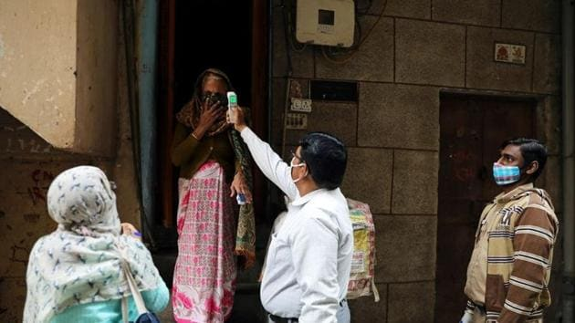A health worker wearing a protective face mask checks the temperature of a woman while conducting door to door survey to identify symptomatic people amid a spike in the Covid-19 cases in New Delhi.(Reuters Photo)