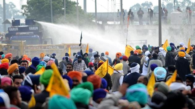 The Haryana Police eventually used water cannons to disperse the farmers, who had gathered in large numbers in tractor-trolleys, when they started removing the concrete barricades. But when that did not deter the farmers, they used tear gas. While it delayed the crossing over, farmers were determined and have continued their march to Delhi. (Bharat Bhushan / HT Photo)