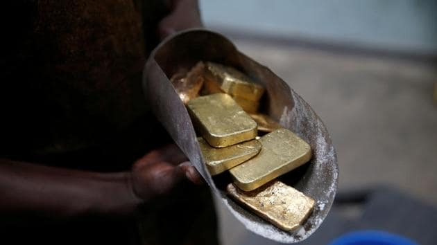 An employee holds gold bars before the refining process in Entebbe, Uganda.(REUTERS)