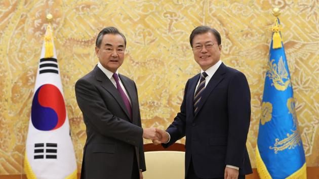 South Korean President Moon Jae-in, right, poses with Chinese Foreign Minister Wang Yi for a photo.(AP)