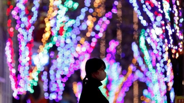 A woman wearing a protective mask, following the coronavirus disease (COVID-19) outbreak, walks past Christmas decorations at a restaurant district in Tokyo, Japan.(Reuters)