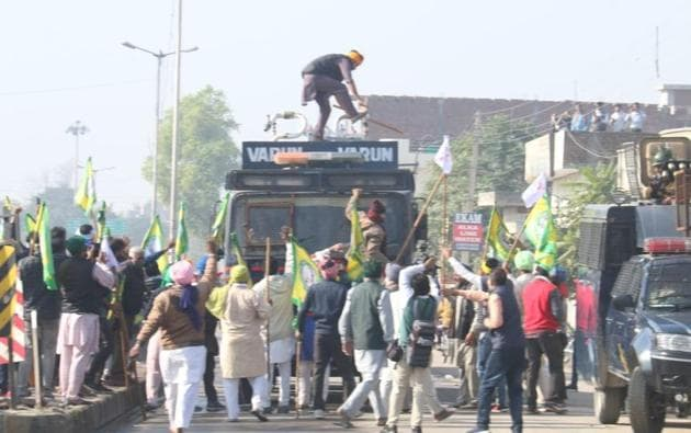 Punjab farmers damaging a riot control vehicle near Dabwal i in Sirsa district on Friday after barging into Haryana on their way to the national capital to protest the three new farm laws.(Sanjeev Kumar/HT)