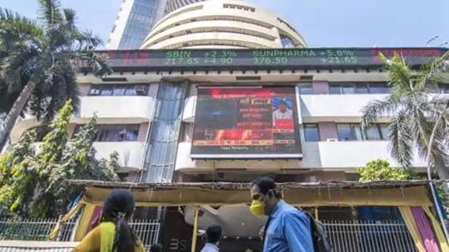 A man walks wearing a mask next to the Bombay stock exchange building.(Pratik Chorge/HT Photo)