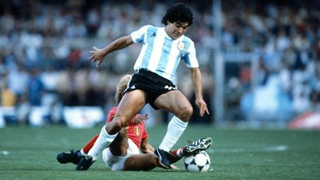 Diego Maradona tackles the ball past a defender.(Getty Images)