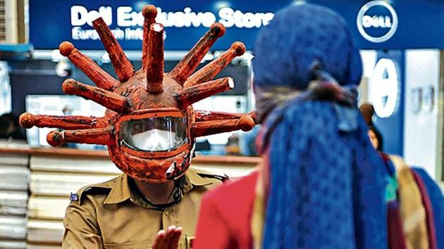 A civil defence volunteer wearing a coronavirus-themed helmet during an awareness campaign at a market in New Delhi(AFP)