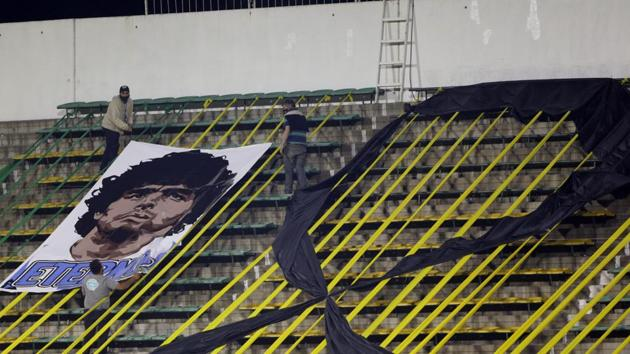 Workers install a banner with the image of Diego Maradona at the Norberto Tomaghello stadium before a Copa Sudamericana Soccer match between Argentina's Defensa y Justicia and Brazil's Vasco Da Gama in Buenos Aires, Argentina, Thursday, Nov. 26, 2020. The Argentine soccer great who was among the best players ever and who led his country to the 1986 World Cup title died from a heart attack at his home Wednesday, at the age of 60. (Daniel Jayo/Pool via AP )(AP)