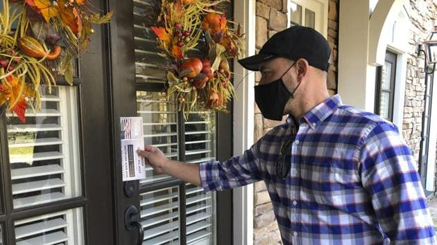 Garrett Bess, vice president of government relations and communications for the conservative activist group Heritage Action For America, leaves information at a residence in a subdivision in Milton.(AP file photo)