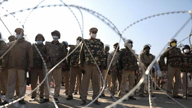 Police officers gather behind barbed wires to stop farmers opposing the newly passed farm bills from entering the national capital Delhi, at Singhu border, India, November 27, 2020.(REUTERS)