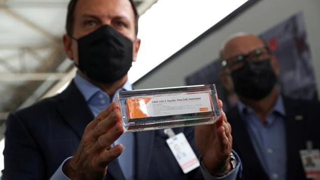 FILE PHOTO: Brazil's Sao Paulo state governor, Joao Doria, and director of Instituto Butantan, Dimas Tadeu Covas, hold boxes of the China's Sinovac vaccine against the coronavirus disease (COVID-19) as a cargo plane containing the vaccines arrives at Sao Paulo International Airport in Guarulhos, Brazil November 19, 2020. REUTERS/Amanda Perobelli/File Photo(REUTERS)