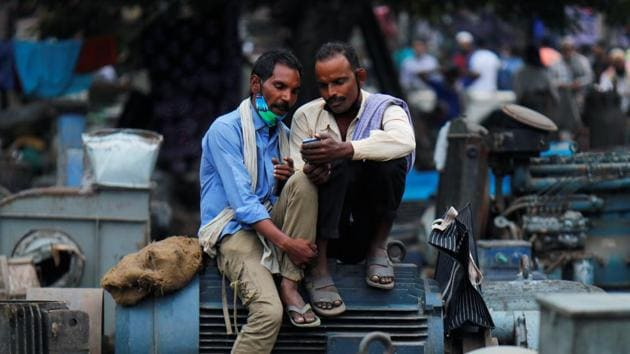Men wearing protective face masks on their chins, amid the coronavirus disease outbreak, watch a video on a mobile phone as they sit at a second-hand motor parts market in the old quarters of Delhi. Economic activity came to a standstill for a large part of the April-June quarter.(REUTERS)