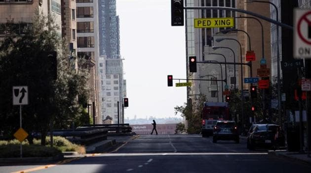 A person crosses an empty Grand Ave in downtown during the outbreak of the coronavirus disease in Los Angeles, California.(REUTERS)