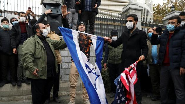 Protesters burn the U.S. and Israeli flags during a demonstration against the the killing of Mohsen Fakhrizadeh.(REUTERS)