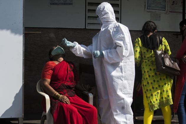 A health worker takes a swab sample of a resident in Govandi on Saturday.(Pratik Chorge/HT Photo)