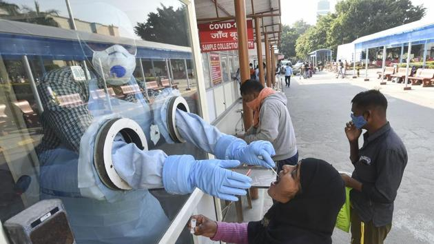 A health worker takes samples for Covid-19 testing at Ram Manohar Lohia Hospital, in Lucknow.(PTI)