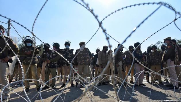 "Police personnel behind barbed wire laid out to impede advancing farmers at Singhu Border on November 27. Most protesters are from Punjab, but there is a substantial number from Haryana as well. There has been scattered support for the ""Delhi Chalo"" protest from Uttar Pradesh, Rajasthan, Madhya Pradesh and Uttarakhand, PTI reported. (Sanchit Khanna / HT Photo)"