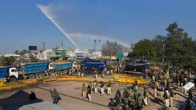 A rainbow forms as a water cannon is fired to disperse farmers at Singhu Border on November 27. While housing arrangements were being ironed out, protesters assembled at Delhi's border at Tigri and Singhu faced tear gas and water cannons to stop them from breaking through barricades, which included sand-laden trucks. (Sanchit Khanna / HT Photo)