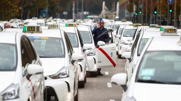 "A taxi driver blows a plastic horn during the ""go-slow"" protest against the lack of support from local authorities towards taxi service providers amid the coronavirus pandemic in Madrid, Spain on November 25. (Sergio Perez / REUTERS)"
