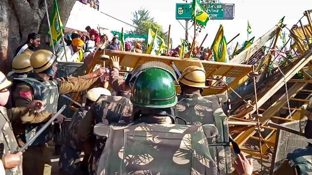 Farmers remove barricades as they head towards Delhi to protest against the farm laws, at Dabwali border on Friday.(ANI)