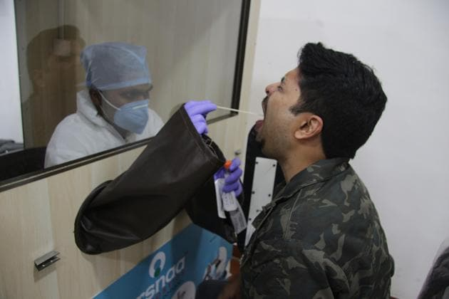 A healthcare worker collects swab samples from passengers at a Covid-19 testing centre at the Pune International Airport, on Saturday.(HT PHOTO)