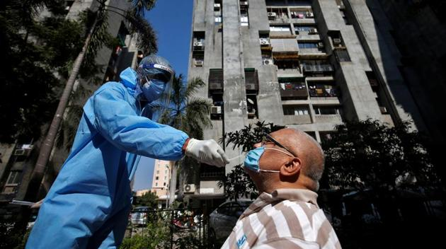 A healthcare worker wearing personal protective equipment (PPE) takes a swab from a man during a testing campaign for the coronavirus disease at a residential area in Ahmedabad.(REUTERS)