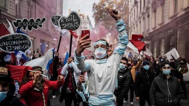 A man gestures while taking a selfie during a protest against the restrictions imposed by the government in wake of the coronavirus pandemic in Lyon, France on November 23. (Jeff Pachoud / AFP)