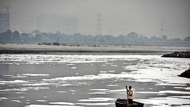 A man rows a boat in the heavily polluted waters of the Yamuna at Kalindi Kunj.