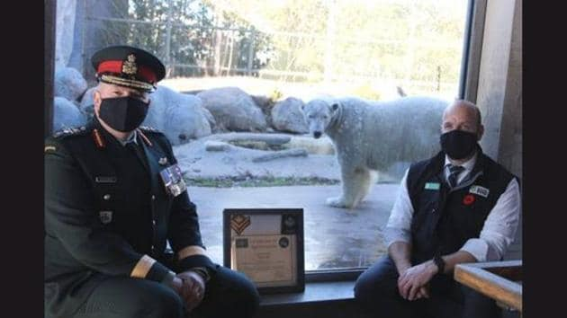 The image shows Juno the polar bear with officials of the Canadian Army.(Twitter/@4CdnDiv4DivCA)
