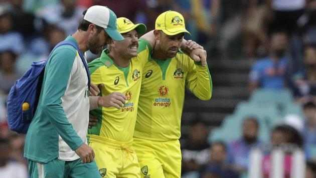 Australia's David Warner, centre, is assisted from the field after injuring himself while fielding during the one day international cricket match between India and Australia at the Sydney Cricket Ground in Sydney, Australia.(AP)