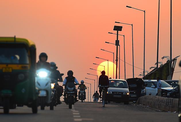 Commuters on NH-24 during sunset on November 26.(Raj K Raj/HT PHOTO)